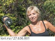 Купить «The senior woman is holding a dumbbell outdoors», фото № 27636801, снято 18 августа 2018 г. (c) PantherMedia / Фотобанк Лори
