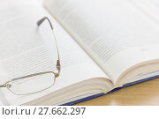 Купить «Close up glasses and open book on the desk», фото № 27662297, снято 1 мая 2018 г. (c) PantherMedia / Фотобанк Лори