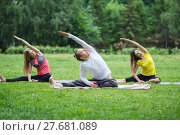 Купить «A group of yoga sportsmen performs breathing exercises in park», фото № 27681089, снято 20 июля 2017 г. (c) Константин Шишкин / Фотобанк Лори