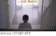 Kid sitting alone on the stairs. Стоковое видео, видеограф Данил Руденко / Фотобанк Лори