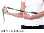 Купить «Woman measuring waist with an inch tape», фото № 27686505, снято 21 сентября 2018 г. (c) PantherMedia / Фотобанк Лори
