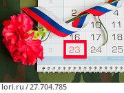 Купить «23 февраля, открытка на день защитника Отечества. Красная гвоздика, российский флаг и календарь с датой 23 февраля на камуфляжной ткани», фото № 27704785, снято 10 апреля 2017 г. (c) Зезелина Марина / Фотобанк Лори