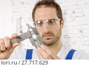 Купить «young man measuring screw using caliper», фото № 27717629, снято 21 мая 2018 г. (c) PantherMedia / Фотобанк Лори