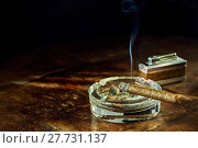 Купить «Smoking cigar sitting in glass ashtray on table», фото № 27731137, снято 25 апреля 2018 г. (c) PantherMedia / Фотобанк Лори