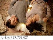 Купить «happy couple with garland lying on floor at home», фото № 27732621, снято 13 января 2018 г. (c) Syda Productions / Фотобанк Лори