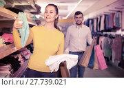 Купить «Happy young woman choosing new towels in store while shopping wi», фото № 27739021, снято 27 декабря 2017 г. (c) Яков Филимонов / Фотобанк Лори