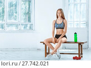 Купить «Muscular young woman athlete sitting with a water on white background», фото № 27742021, снято 25 апреля 2019 г. (c) PantherMedia / Фотобанк Лори