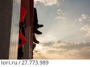 Купить «People sit on the ferry, his legs dangling over sea.», фото № 27773989, снято 20 августа 2018 г. (c) PantherMedia / Фотобанк Лори