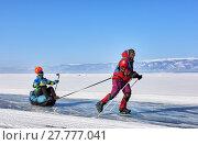 Купить «Активный отдых на льду Байкала. Мужчина на коньках катает девушку в волокушах», фото № 27777041, снято 8 марта 2017 г. (c) Виктор Никитин / Фотобанк Лори