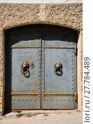 Купить «Old iron door with lion handles on a stone wall», фото № 27784489, снято 22 апреля 2019 г. (c) PantherMedia / Фотобанк Лори