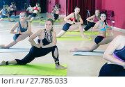 Купить «Women exercising yoga poses in fitness center», фото № 27785033, снято 31 мая 2017 г. (c) Яков Филимонов / Фотобанк Лори