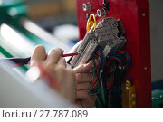 Купить «Hands of electrician engineer screwing and testing equipment in fuse box», фото № 27787089, снято 12 февраля 2018 г. (c) Константин Шишкин / Фотобанк Лори