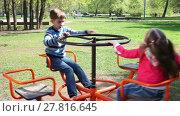 Купить «Happy children have fun on spinning roundabout at playground», видеоролик № 27816645, снято 10 мая 2016 г. (c) Алексей Кузнецов / Фотобанк Лори