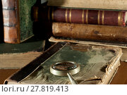 Купить «An ancient book in a ragged cover and a magnifying glass on a table closeup on a blurred background of other old books», фото № 27819413, снято 20 декабря 2017 г. (c) Евгений Харитонов / Фотобанк Лори
