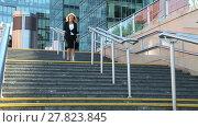 Купить «Business woman down the stairs of the business center and talking on a cell phone», видеоролик № 27823845, снято 8 июля 2015 г. (c) Алексей Кузнецов / Фотобанк Лори