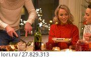 Купить «happy friends having christmas dinner at home», видеоролик № 27829313, снято 22 декабря 2017 г. (c) Syda Productions / Фотобанк Лори