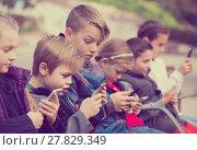 Купить «Outdoor portrait of girls and boys playing with phones», фото № 27829349, снято 19 июня 2019 г. (c) Яков Филимонов / Фотобанк Лори