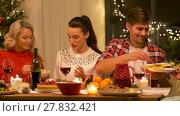 Купить «happy friends having christmas dinner at home», видеоролик № 27832421, снято 22 декабря 2017 г. (c) Syda Productions / Фотобанк Лори