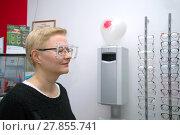 Купить «Девушка у аппарата для подбора оправы для очков в салоне оптики», фото № 27855741, снято 14 февраля 2018 г. (c) Виктор Карасев / Фотобанк Лори