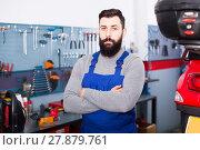 Купить «bearded man worker displaying his workplace in motorcycle workshop», фото № 27879761, снято 23 февраля 2018 г. (c) Яков Филимонов / Фотобанк Лори