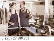 Купить «Workman 20-30 years old is explaining work on circular saw to yo», фото № 27880833, снято 19 июля 2017 г. (c) Яков Филимонов / Фотобанк Лори