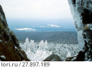 View in cloudy weather on winter wooded hills from the top of the mountain in a gap between two natural stone boulders. Стоковое фото, фотограф Евгений Харитонов / Фотобанк Лори