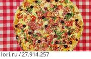 Купить «Front view video of rotating pizza with cheese, tomatoes and olives on the red tablecloth», видеоролик № 27914257, снято 13 марта 2016 г. (c) Алексей Кузнецов / Фотобанк Лори
