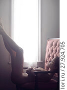 Купить «Artistic nude sensual portrait of a beautiful woman with a dreamy expression lying naked in an armchair with her legs raised up agaist the window in bright sunlight.», фото № 27924705, снято 20 января 2018 г. (c) age Fotostock / Фотобанк Лори