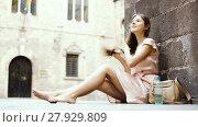 Купить «young happy female in rose dress sitting in city», видеоролик № 27929809, снято 8 сентября 2017 г. (c) Яков Филимонов / Фотобанк Лори