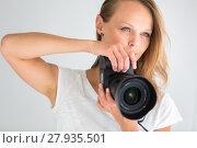 Купить «Pretty, female photographer with digital camera - DSLR and a huge telephoto lens (color toned image; shallow DOF)», фото № 27935501, снято 19 июля 2018 г. (c) PantherMedia / Фотобанк Лори