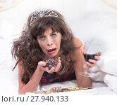 Купить «Sobbing Woman in Tiara Drinking Wine and Cramming Chocolates in Bedroom», фото № 27940133, снято 20 марта 2018 г. (c) PantherMedia / Фотобанк Лори