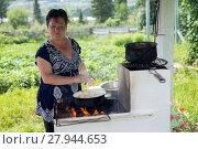 Купить «Женщина готовит еду на самодельной печи, летом на даче», фото № 27944653, снято 16 июля 2017 г. (c) Светлана Попова / Фотобанк Лори