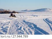 Снегоход с двумя рыбаками едет по замёрзшему озеру. Стоковое фото, фотограф Светлана Попова / Фотобанк Лори