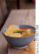 Купить «Chicken noodle soup in a blue and white bowl with crackers, all sitting on a wood cutting board. », фото № 27957709, снято 22 июля 2019 г. (c) PantherMedia / Фотобанк Лори