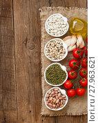 Купить «Legumes in bowls, tomatoes, garlic and olive oil on wooden table», фото № 27963621, снято 19 февраля 2019 г. (c) PantherMedia / Фотобанк Лори