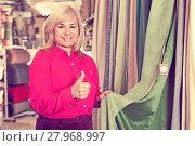 Купить «seller showing curtain and holding thumb up», фото № 27968997, снято 17 января 2018 г. (c) Яков Филимонов / Фотобанк Лори