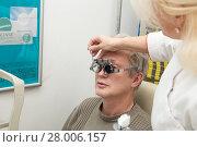 Купить «Man in optometric clinic. Eyesight check with trial frame», фото № 28006157, снято 13 февраля 2018 г. (c) Юлия Бабкина / Фотобанк Лори