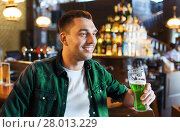 Купить «man drinking green beer at bar or pub», фото № 28013229, снято 22 апреля 2015 г. (c) Syda Productions / Фотобанк Лори