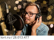 Купить «man with headphones singing at recording studio», фото № 28013477, снято 18 августа 2016 г. (c) Syda Productions / Фотобанк Лори