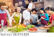 Купить «happy friends and chef cook cooking in kitchen», фото № 28013825, снято 12 февраля 2015 г. (c) Syda Productions / Фотобанк Лори