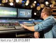 Купить «man at mixing console in music recording studio», фото № 28013881, снято 18 августа 2016 г. (c) Syda Productions / Фотобанк Лори