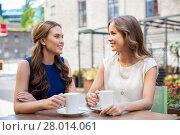 Купить «happy young women drinking coffee at outdoor cafe», фото № 28014061, снято 9 августа 2015 г. (c) Syda Productions / Фотобанк Лори