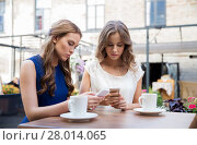 Купить «young women with smartphones and coffee at cafe», фото № 28014065, снято 9 августа 2015 г. (c) Syda Productions / Фотобанк Лори
