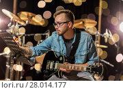 Купить «man with guitar writing to music book at studio», фото № 28014177, снято 18 августа 2016 г. (c) Syda Productions / Фотобанк Лори