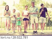 Купить «Young family with children looking at phone», фото № 28022781, снято 25 сентября 2018 г. (c) Яков Филимонов / Фотобанк Лори