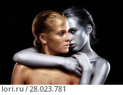 Купить «Golden and silver girls on black background. Silver female hugging a golden one», фото № 28023781, снято 17 февраля 2018 г. (c) Serg Zastavkin / Фотобанк Лори