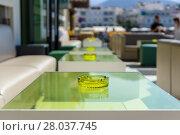 Купить «An empty table with an ashtray in a street restaurant. Focus on the foreground.», фото № 28037745, снято 25 апреля 2018 г. (c) PantherMedia / Фотобанк Лори