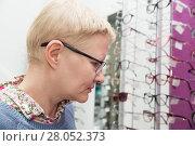Купить «Woman chooses new frame for glasses in the store optics», фото № 28052373, снято 13 февраля 2018 г. (c) Юлия Бабкина / Фотобанк Лори