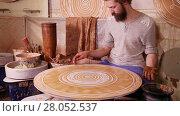 Купить «Craftsman creating a decorative circular panel on a spinning wheel», видеоролик № 28052537, снято 24 марта 2016 г. (c) Алексей Кузнецов / Фотобанк Лори
