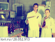 Купить «Two happy employees standing in packaging section on wine manufactory», фото № 28052913, снято 21 сентября 2016 г. (c) Яков Филимонов / Фотобанк Лори